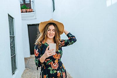Spain, Cadiz, Vejer de la Frontera, fashionable woman looking at mobile phone - p300m2103992 von Kiko Jimenez