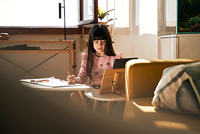 Portrait of girl doing homework in the living room - p300m2188502 by Eloisa Ramos