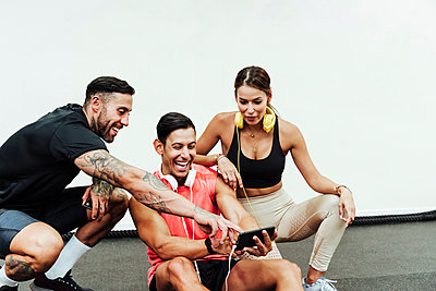 Cheerful friends looking at mobile phone while crouching at gym - p300m2274525 by Eva Blanco