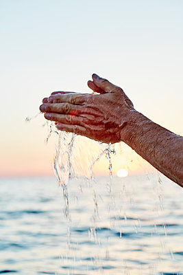 Hand touching water - p312m1113926f by Magnus Ragnvid