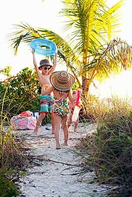 Boy and two sisters playing and collecting seashells at beach, Sanibel, Florida, USA - p924m1094782f by Kinzie Riehm