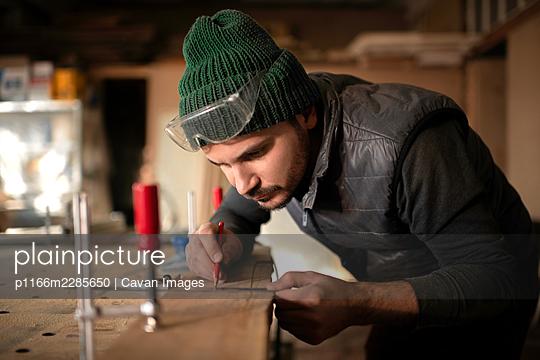 Focused craftsman making marks on board - p1166m2285650 by Cavan Images