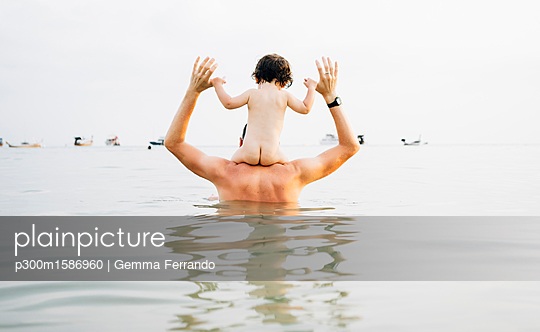 Back view of father carrying his little daughter on shoulders in the sea - p300m1586960 von Gemma Ferrando