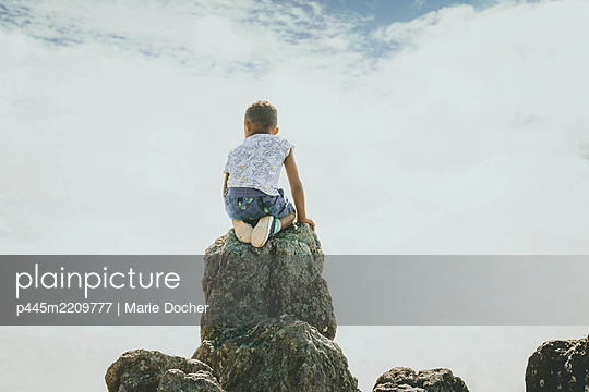 child on a rock - p445m2209777 by Marie Docher