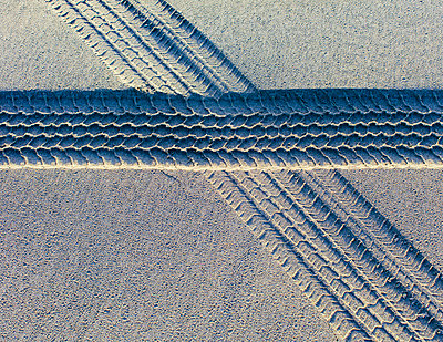 Tire tracks on the soft surface of sand on a beach.  - p1100m2085136 by Mint Images