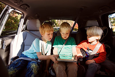 Brothers looking at tablet computer while sitting in car - p1166m1096492f by Cavan Images