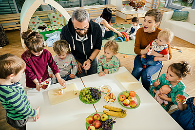 Group of children and teachers preparing fruit in kindergarten - p300m1537479 by Mareen Fischinger
