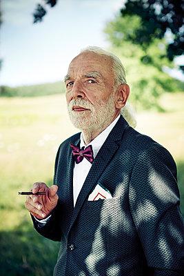 Portrait of senior man wearing suit coat, bow tie and dress handkerchief in nature smoking cigarillo - p300m2081361 by Viviane Wild