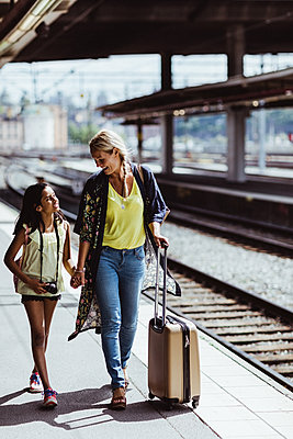 Smiling mother and daughter with luggage talking while walking at station - p426m2146057 by Maskot