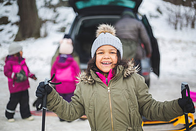 Portrait of smiling girl holding ski poles during winter - p426m2284837 by Maskot
