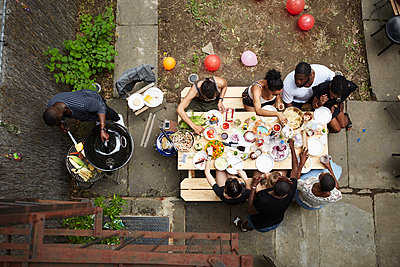 High angle view of friends enjoying backyard barbecue - p555m1409851 by Granger Wootz