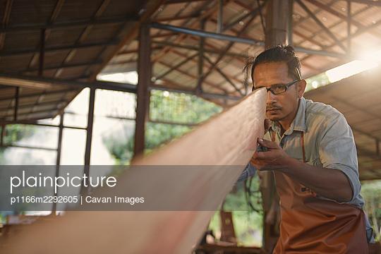 Carpenters using circular saw in workshop - p1166m2292605 by Cavan Images