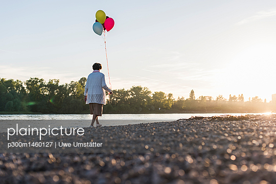 Back view of senior woman with balloons strolling at riverside - p300m1460127 by Uwe Umstätter