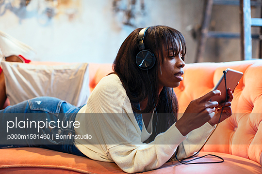 Young woman lying on the couch using tablet and headphones - p300m1581460 von Bonninstudio