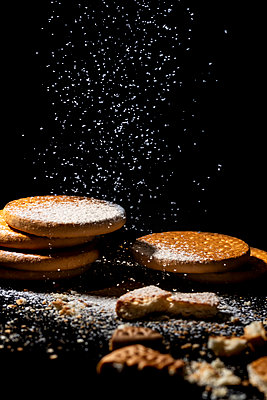 Artisan cookies piled on a black background with powdered sugar glass - p1166m2192022 by Cavan Images