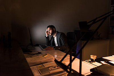 Pensive young businessman sitting at desk in office at night - p300m1581321 von Uwe Umstätter