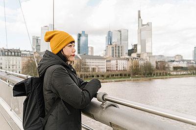 Woman on a bridge enjoying the view, Frankfurt, Germany - p300m2179997 by Hernandez and Sorokina