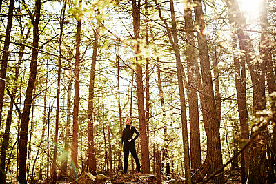 Woman in sportswear standing in forest - p343m2046833 by Josh Campbell