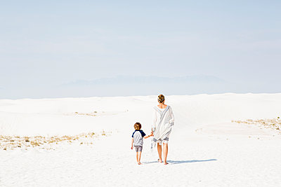 Caucasian mother and son walking in sand - p555m1521425 by Marc Romanelli