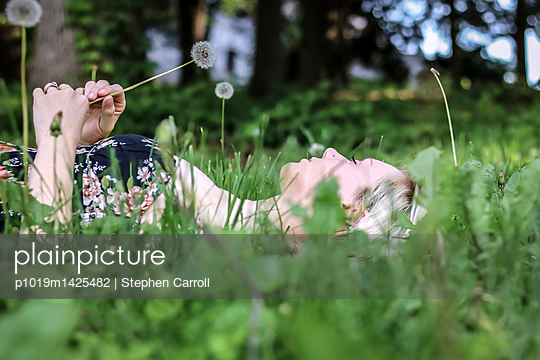 Blonde woman lying in the grass - p1019m1425482 by Stephen Carroll