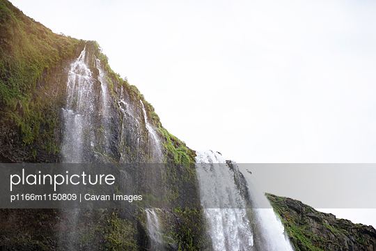 Low angle view of Seljalandsfoss Waterfall against sky - p1166m1150809 by Cavan Images