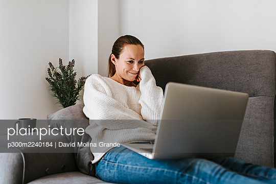 Caucasian woman watching video on laptop at home - p300m2240184 by David Molina Grande