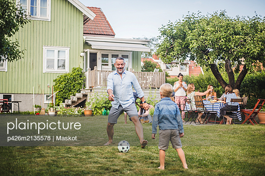 Father playing football with son while friends having fun at table in backyard party - p426m2135578 by Maskot