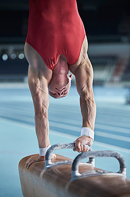 Male gymnast performing upside-down handstand on pommel horse - p1023m1217737 by Chris Ryan