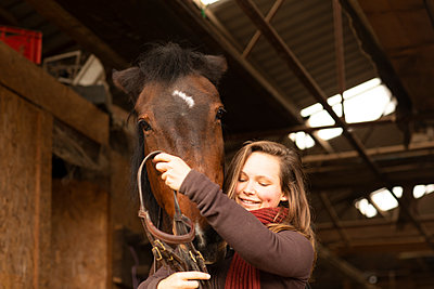 young woman with a horse in a horse stable with bridles - p1166m2148590 by Cavan Images