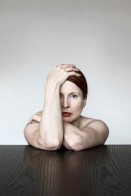 Portrait einer Frau am Tisch mit Hand auf dem Kopf - p1574m2183642 von manuela deigert