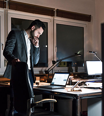 Businessman standing in office at night looking at laptop - p300m1581219 by Uwe Umstätter