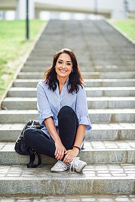 Portrait of smiling student sitting on stairs outdoors - p300m2060273 von Javier Sánchez Mingorance