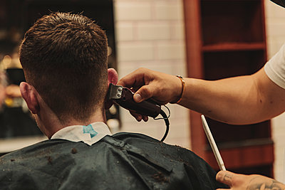 Male barber using clipper for cutting customer's hair in salon - p300m2287105 by Aitor Carrera Porté