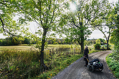 Woman with cart on dirt track - p312m2101714 by Pernille Tofte