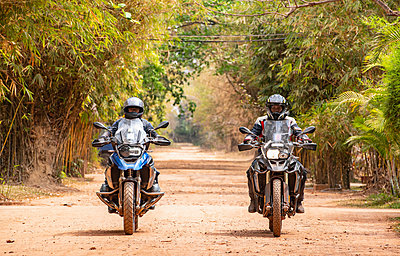 Two male friends riding ADV motorcycles on rural road in Cambodia - p429m2091594 by Henn Photography