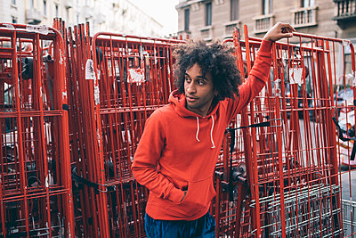 Young man waiting beside steel frames - p429m2098161 by Eugenio Marongiu