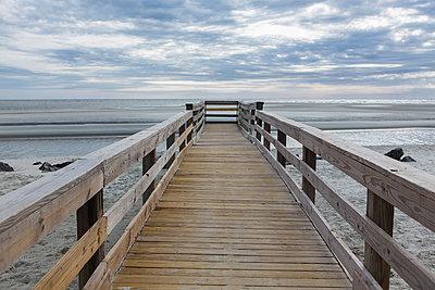 Wooden pier over beach - p555m1453239 by Marc Romanelli