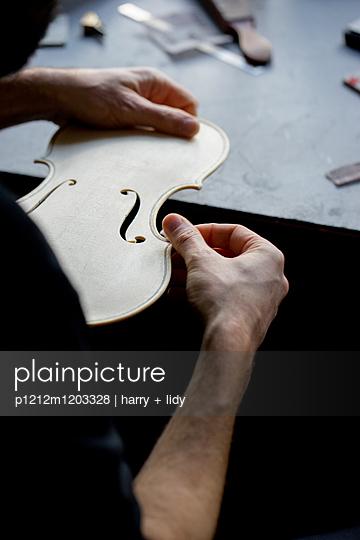 Geigenbauer schleift die Decke einer neuen Geige - p1212m1203328 von harry + lidy