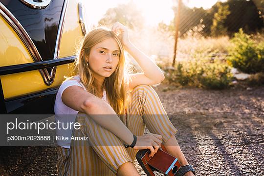 Young woman holding vintage camera sitting outside at a van - p300m2023888 von Kike Arnaiz