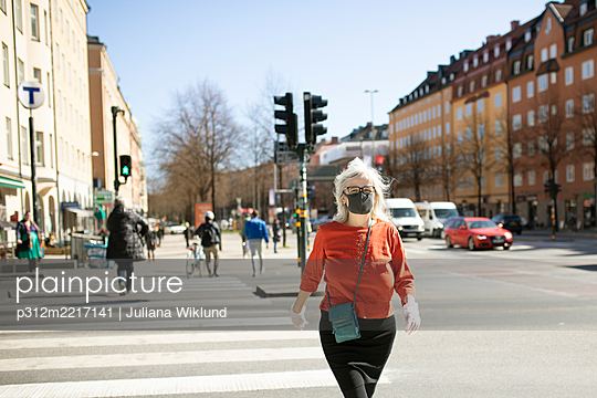 Woman wearing face mask while crossing street - p312m2217141 by Juliana Wiklund