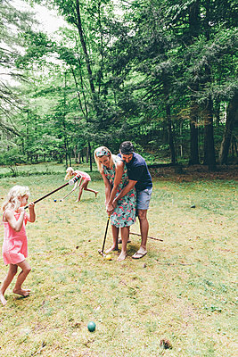 Family playing croquet - p1086m2149973 by Carrie Marie Burr