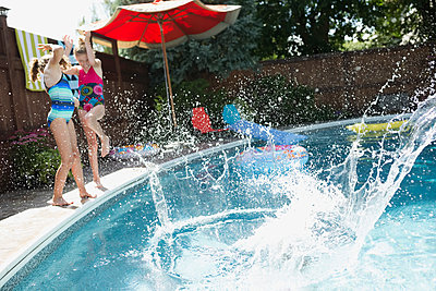 Water splashing girls at sunny poolside - p1192m1183972 by Hero Images