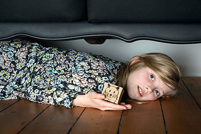 Girl lying on floor holding box with painted mouse - p300m1449979 by Petra Stockhausen