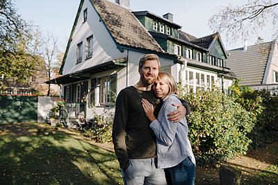 Portrait of smiling couple standing in front of their home - p300m2205504 by Kniel Synnatzschke