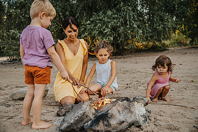 Mature woman and children making barbecue at beach - p300m2221563 by Mareen Fischinger