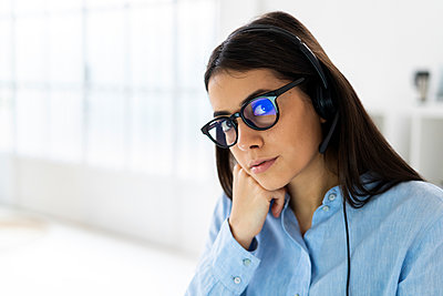 Businesswoman wearing microphone headset and eyeglasses staring while sitting at office - p300m2251412 by Giorgio Fochesato