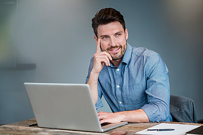 Thoughtful smiling businessman with laptop over table at work place - p300m2274241 by Daniel Ingold