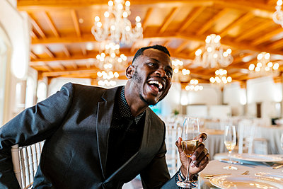 Handsome man holding champagne flute while sitting by table at banquet - p300m2275021 by Ezequiel Giménez