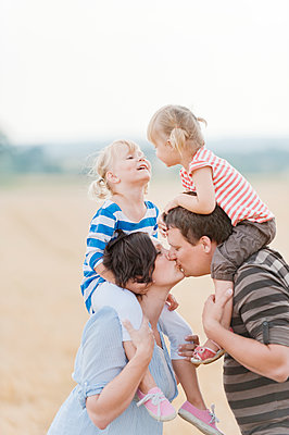 Family with two children kissing in field - p312m1113852f by Rebecca Wallin