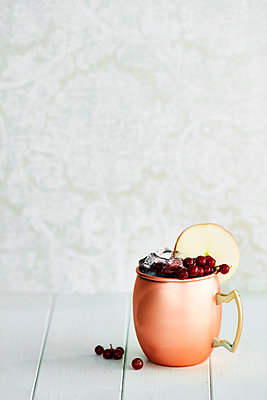 Non-alcoholic cocktail in copper mug with berries and apple slice - p429m1224299 by Debby Lewis-Harrison